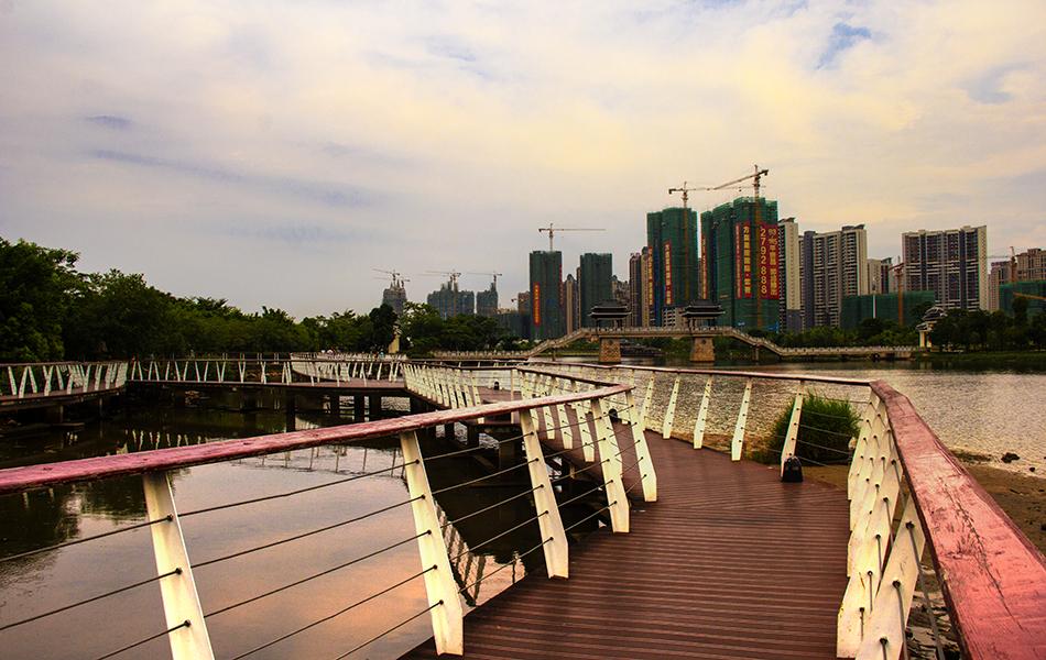 """除了连接""""长桥鱼跃""""的小径,还有搭在水央上的栈道。朱红色的桥面还有扶栏与远处的凉亭相呼应。"""